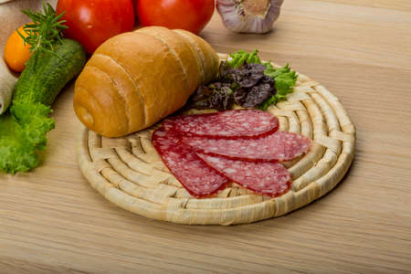 Salami sausages sliced with basil and bread photo