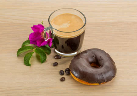 Chocolate donuts with coffee on the desk photo