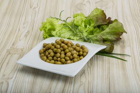 vegetable tin: Marinated peas - in the bowl with salad leaves Stock Photo