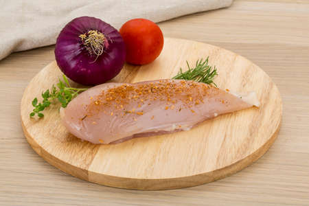 Raw chicken breast - with spices and herbs ready for cooking photo