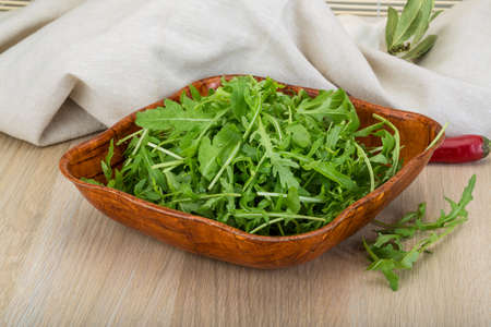 ruccola: Ruccola leaves mix in the bowl on wooden background
