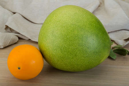 pummelo: Green pomelo and orange on the wood background Stock Photo
