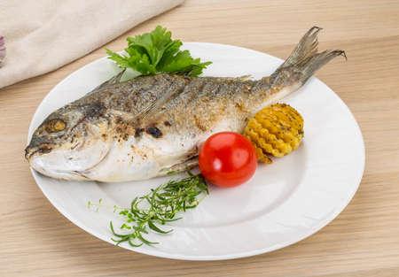 pescado frito: Pescado a la plancha - dorado con hierbas en la mesa