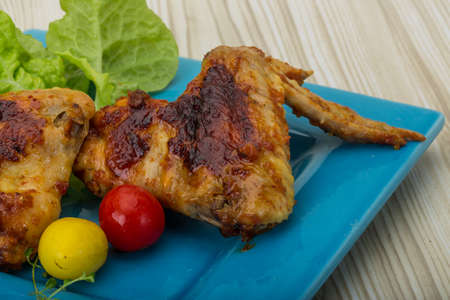 Chicken wings roasted - served with salad leaves, thyme and tomato Stock Photo