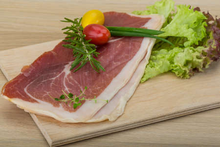 Prosciutto with rosemary, onion, salad leaves and thyme photo