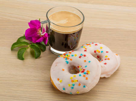 Glazed donuts with coffee on the desk photo