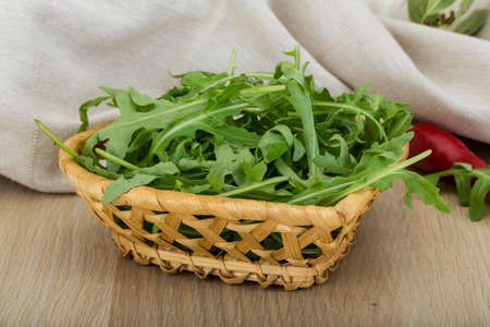 Ruccola leaves mix in the bowl on wooden