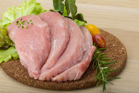 schnitzel: Raw pork schnitzel with rosemary and thyme