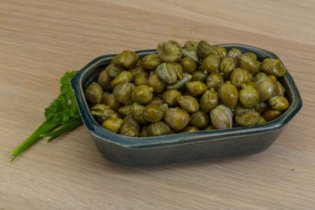 alcaparras: Alcaparras en el recipiente con hojas verdes Foto de archivo