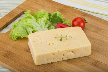 yellow block: Block of Yellow cheese with herbs on wood