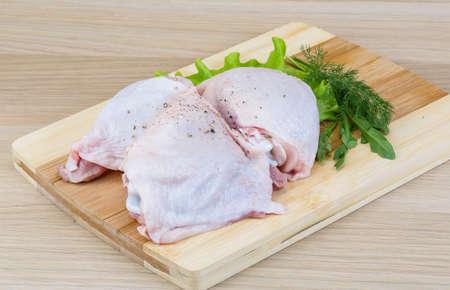 muslos: Muslos de pollo crudo con hojas de ensalada y r�cula Foto de archivo