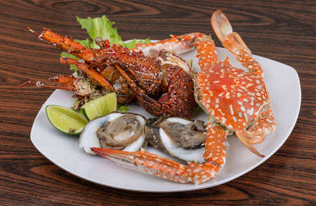 Spiny lobster, crab and oyster on the bowl with lime