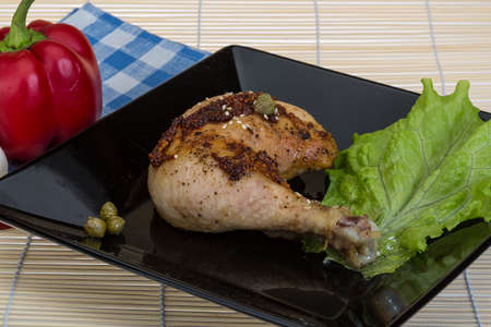 Roasted chicken leg with fresh herbs and spices photo