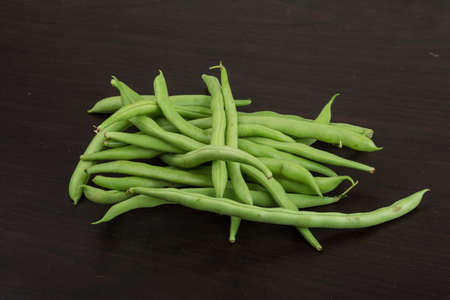 Fresh ripe Green beans heap on the wooden background photo
