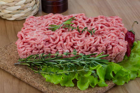 Raw minced meat with rosemary and thyme ready for cooking