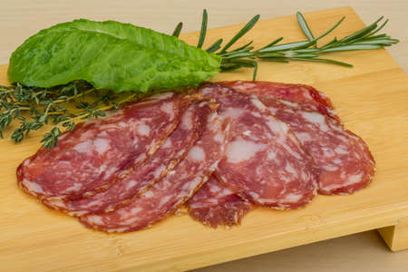 Sliced Salami with herbs on the wooden bckground photo
