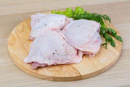 Raw chicken thighs with salad leaves and ruccola