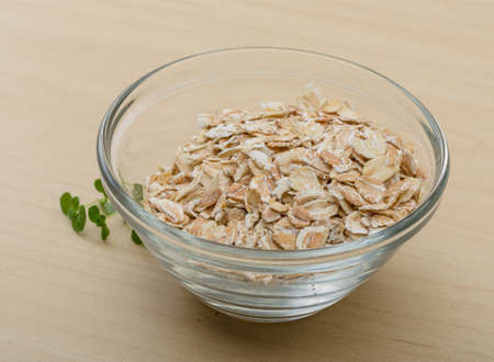 Dry oats pile in the glass bowl photo