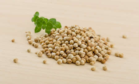 coriander seeds: Coriander seeds heap on the wood background Stock Photo