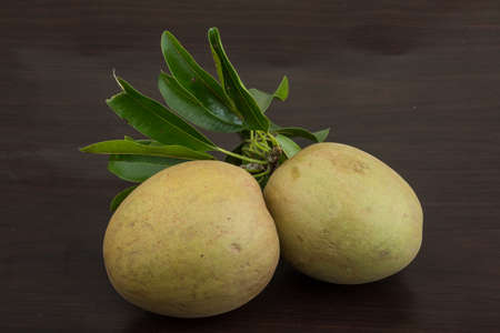 Asian fruit Sapodilla with leaves - on wood background photo