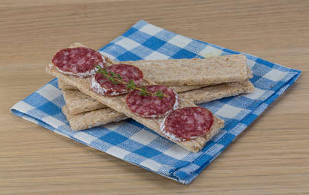 rucola: Crispbread with salami and fresh rucola leaves