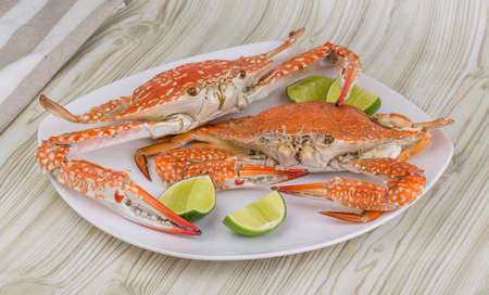 Boiled crabs with lime on the wood background photo