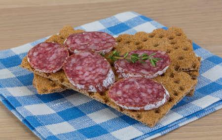 Crispbread with salami and fresh rucola leaves photo