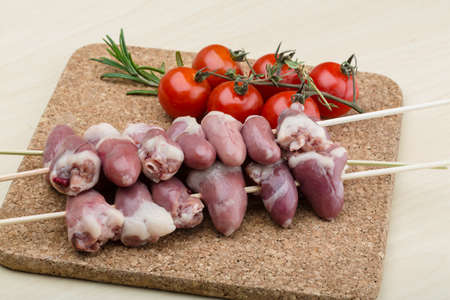Raw chicken hearts ready for barbecue with rosemary photo