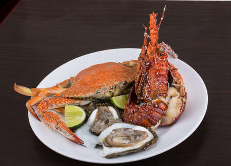 spiny lobster: Spiny lobster, crab and oyster on the bowl with lime