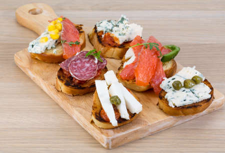 tapas españolas: Tapas con queso, salami, salmón, tomate y hierbas Foto de archivo