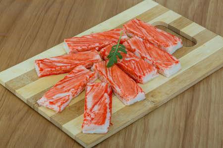 ruccola: Crab sticks with ruccola leaf on the wood