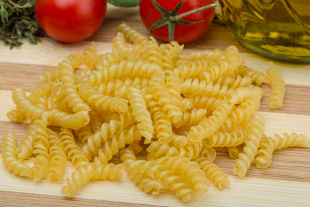 rotini: Raw rotini pasta on the wood background