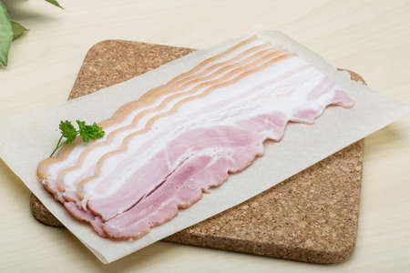 raw bacon: Raw Bacon strips on the wood