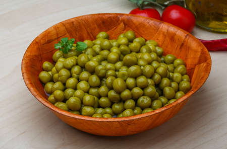 vegetable tin: Green canned peas in the bowl on the wood  Stock Photo