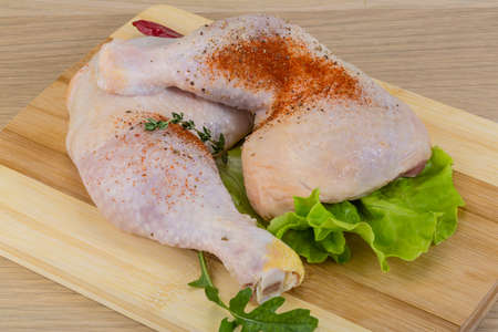 Raw chicken leg with herbs ready for cooking photo