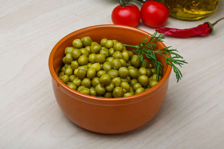 canned peas: Green canned peas in the bowl on the wood background