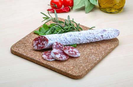 embutido: Spanish sausage - fuet salami with rosemary and salad Stock Photo