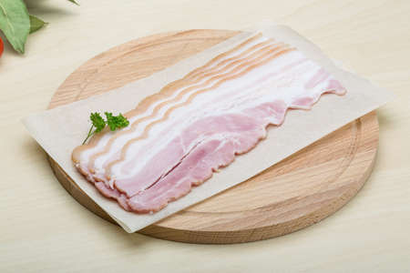 raw bacon: Raw Bacon strips on the wood background Stock Photo