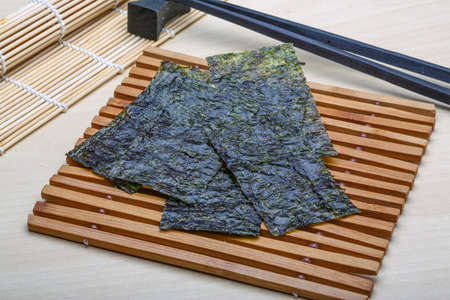 nori: Nori sheets with sticks on the wood background