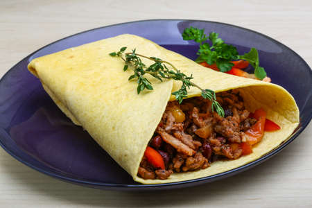 mexican food: Burrito with herbs on the wood background Stock Photo
