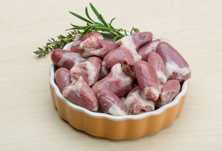 giblets: Raw chicken hearts with thyme and rosemary - ready for cooking
