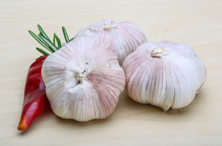 Garlic heads with rosemary on wood background photo