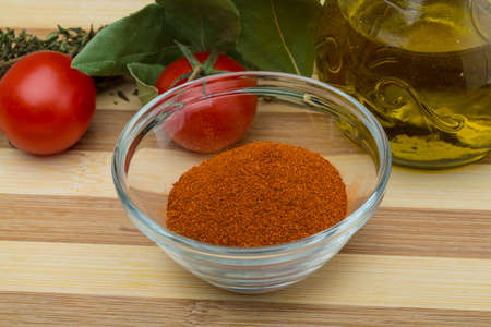 Paprika powder in the glass bowl on wood background photo