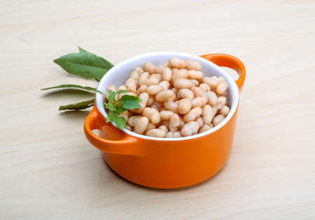 White canned beans in the bowl with herbs photo