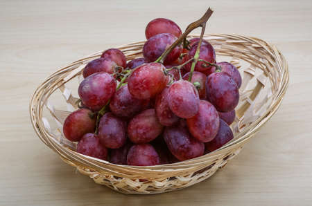 Red ripe grape on the wood background photo