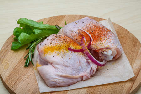 Two Raw chicken thights with herbs and spices photo