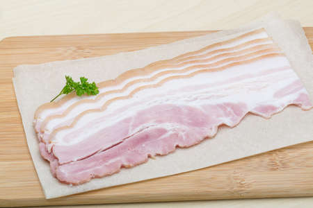 Raw Bacon strips on the wood background photo