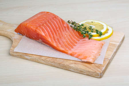 Salted Salmon on the wood background with herbs photo