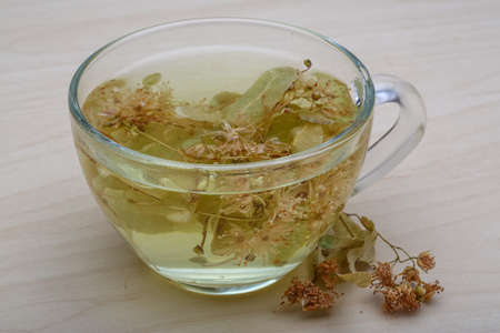 lime blossom: Linden tea in the glass on wood background Stock Photo