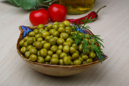vegetable tin: Green canned peas in the bowl on the wood background